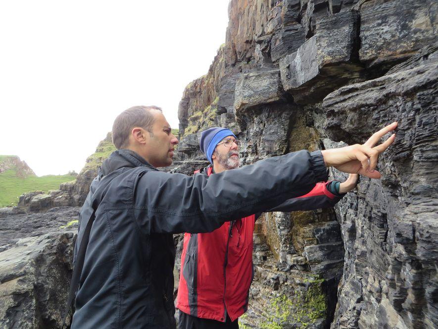 Steve Brusatte (à esquerda) e Mark Wilkinson examinam a face do penhasco diretamente adjacente ao sítio ...
