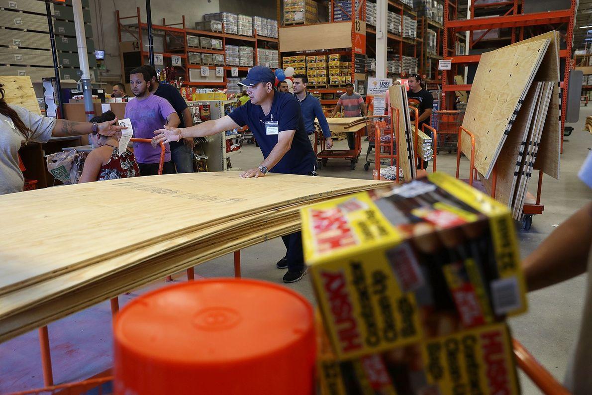Pessoas compram madeira compensada em loja como preparação para o furacão Irma em 6 de setembro ...