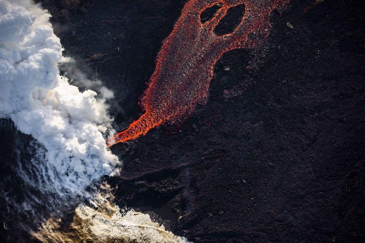 Uma corrente de lava a 2.000ºC chega ao oceano. Ao entrarem em contato, a água do ...