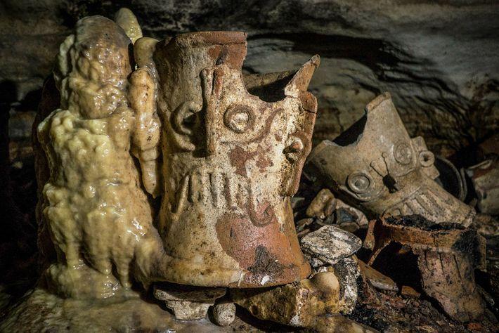 o longo dos séculos, formaram-se estalagmites ao redor de objetos de rituais como este incensário, que ...