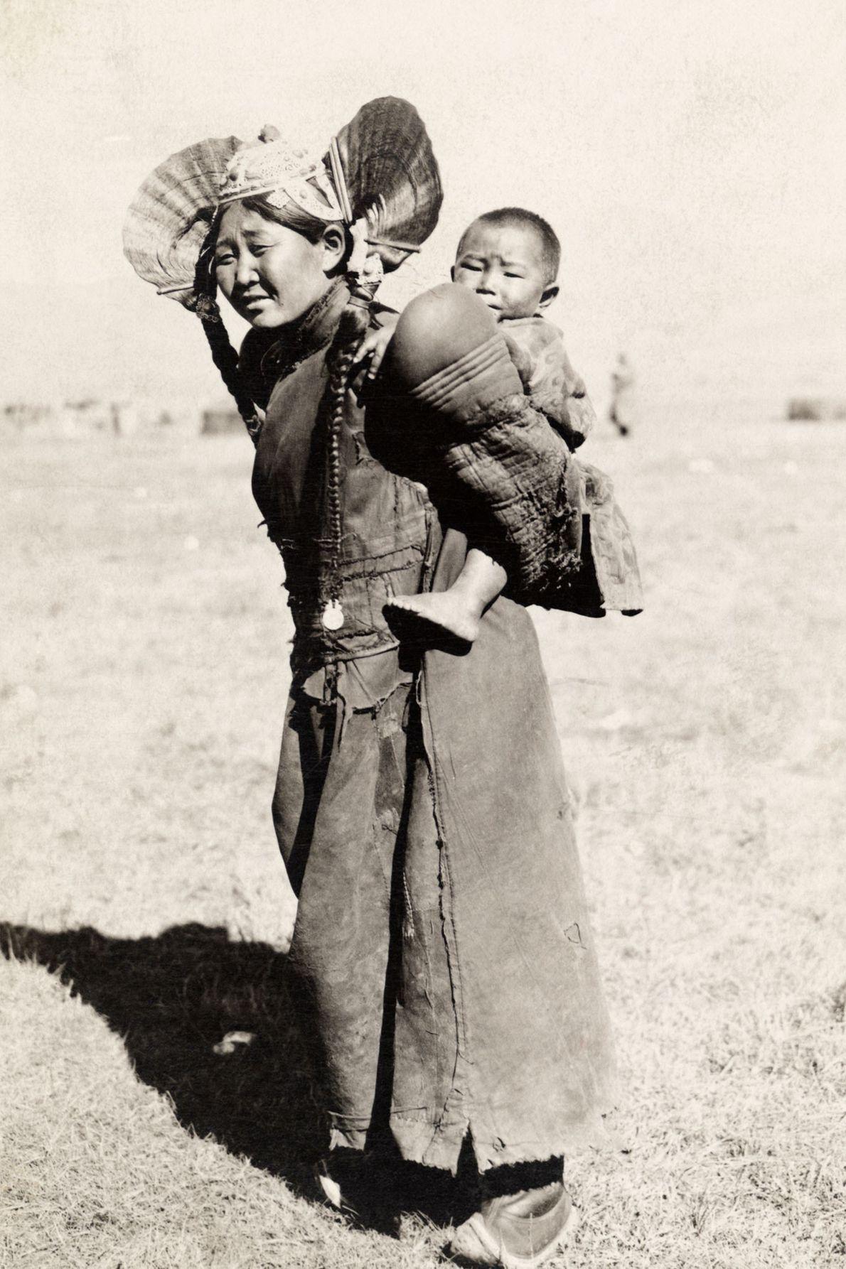 Vestida com roupas tradicionais, uma mãe do norte da Mongólia carrega seu filho nas costas.