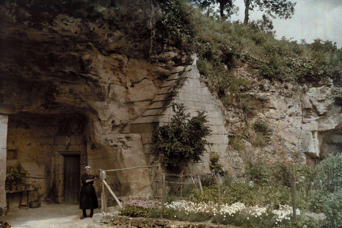 Uma mulher em frente a uma igreja em uma caverna na vila de Courtineau, na França.