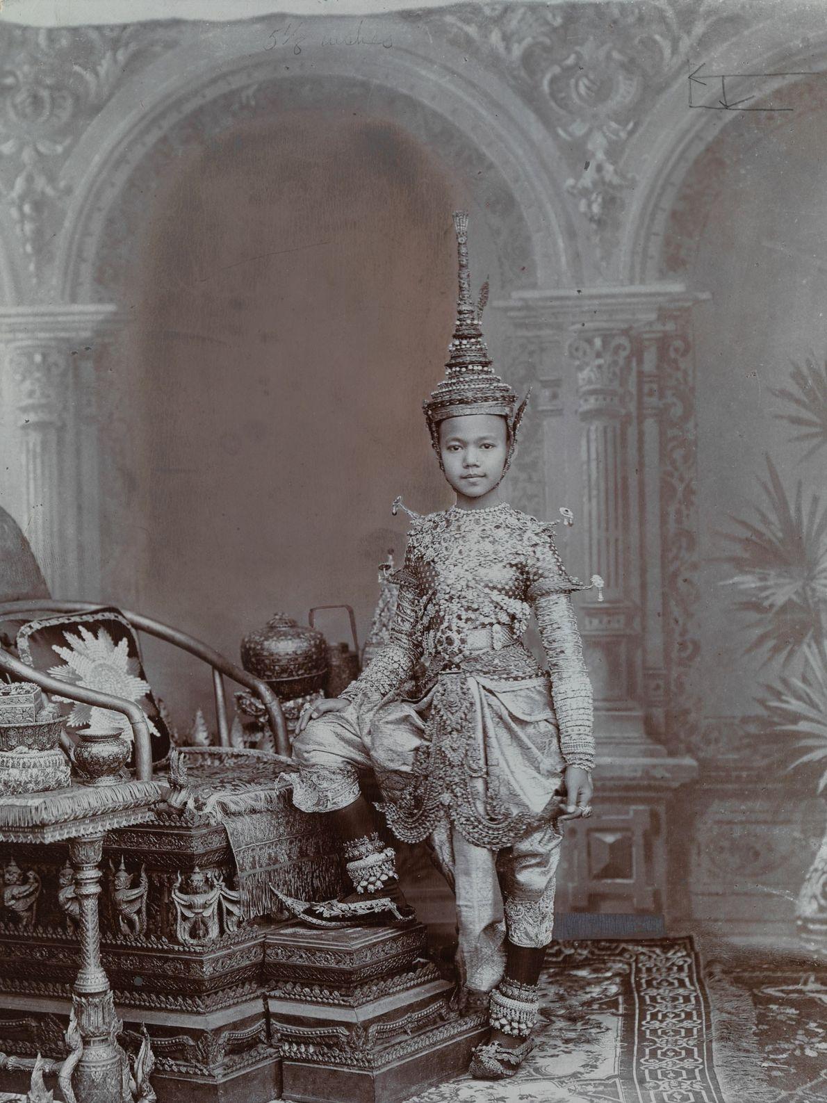 Um príncipe do Sião usa um completo conjunto de joias, incluindo o chapéu no modelo de ...