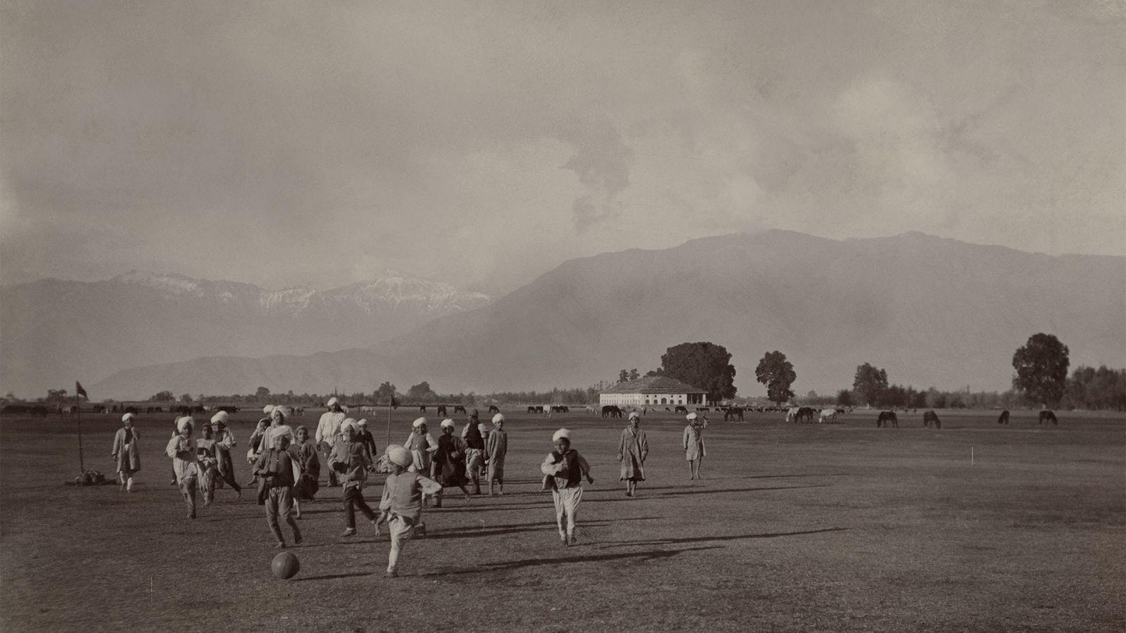 Em um campo vasto nos pés do Himalaia, crianças jogam futebol.