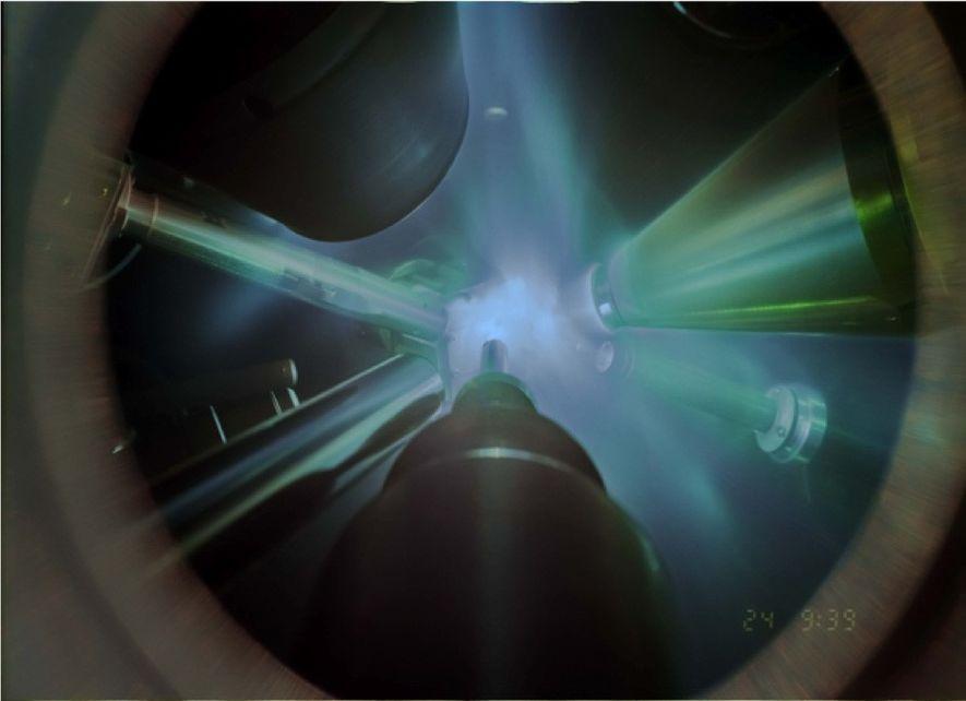 Nessa foto de um experimento de difração de raio-X, lasers gigantes focam a amostra de água, ...
