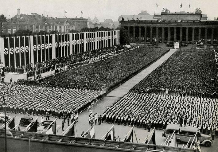 A chama olímpica chega a um estádio repleto de suásticas na Cerimônia de Abertura dos Jogos ...