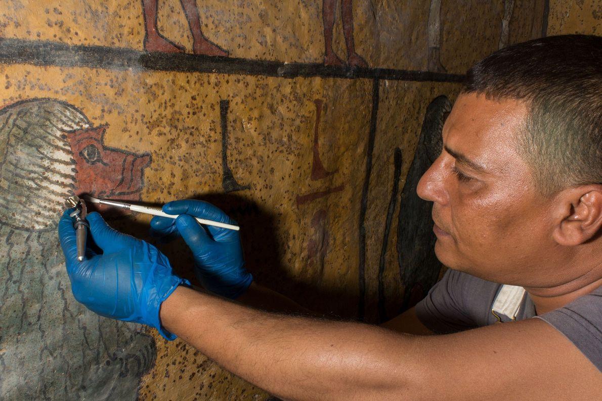 Conservador sopra suavemente a poeira pegajosa acumulada nas superfícies pintadas da tumba de Tutancâmon.
