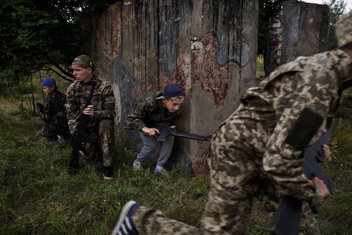 Crianças ucranianas participam de uma simulação militar no acampamento RANGER. O programa de treinamento militar patriota ...