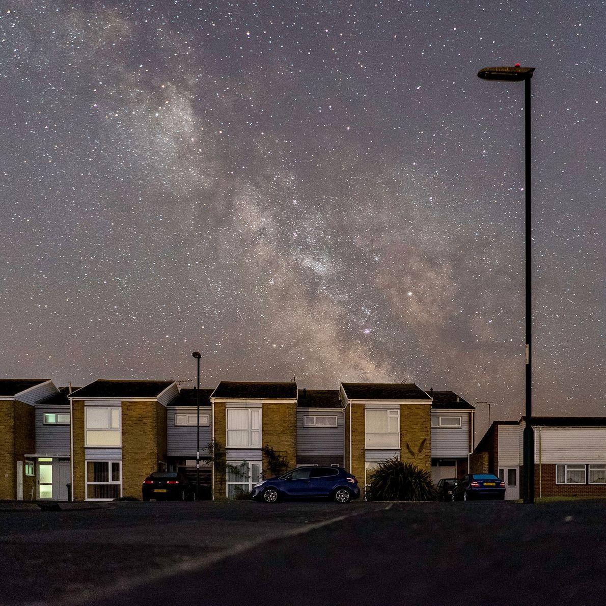 Postes de luz apagados revelam uma vista espetacular das estrelas sobre a vila costeira, Pagham, em ...