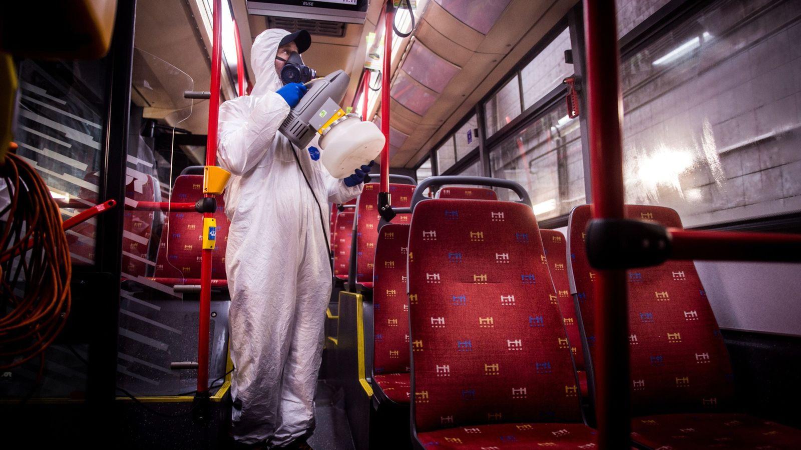 Funcionário com vestimenta de proteção desinfeta o interior de um ônibus público em uma estação de ...