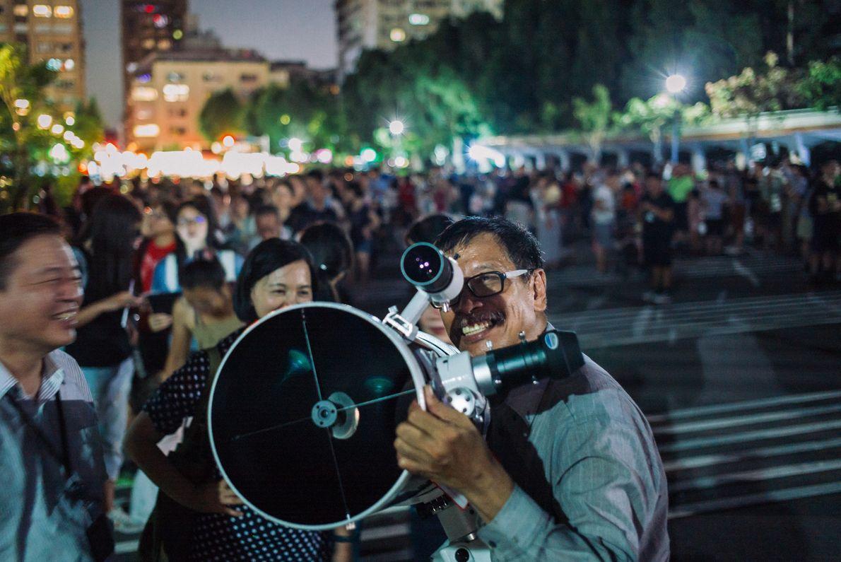 Observadores tentam configurar um telescópio para ver o raro eclipse lunar total próximo ao Memorial Nacional ...