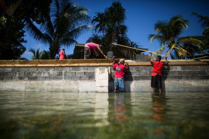 Pessoas reconstruindo um paredão em Ejit para tentar conter a subida da água.