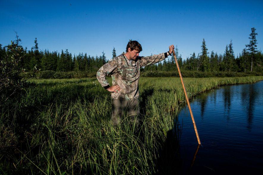 Nikita Zimov faz bolhas de metano em um lago que é possível que esteja aumentando devido ao derretimento do solo.