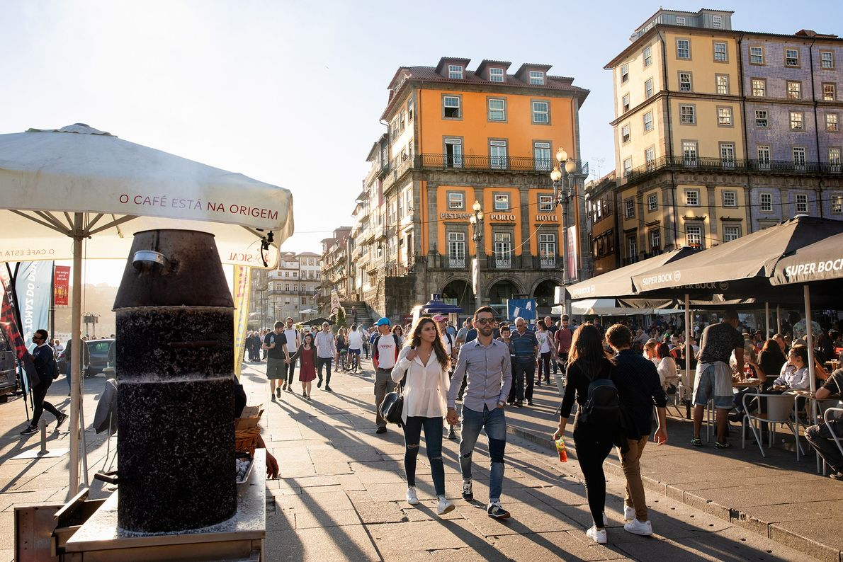 Pedestres passeiam pelas barracas de castanhas e cafés do calçadão da orla do Porto em uma ...