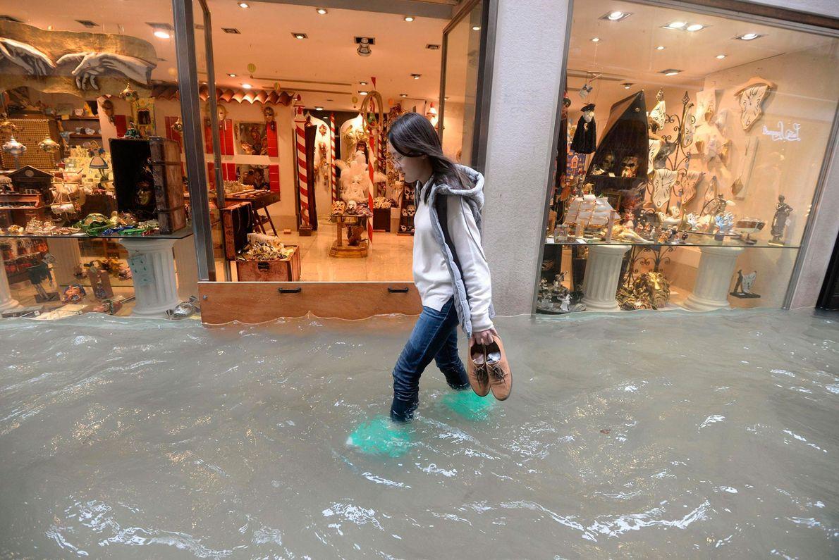 Uma mulher caminha em uma rua alagada de Veneza. De acordo com os oficiais da cidade, ...