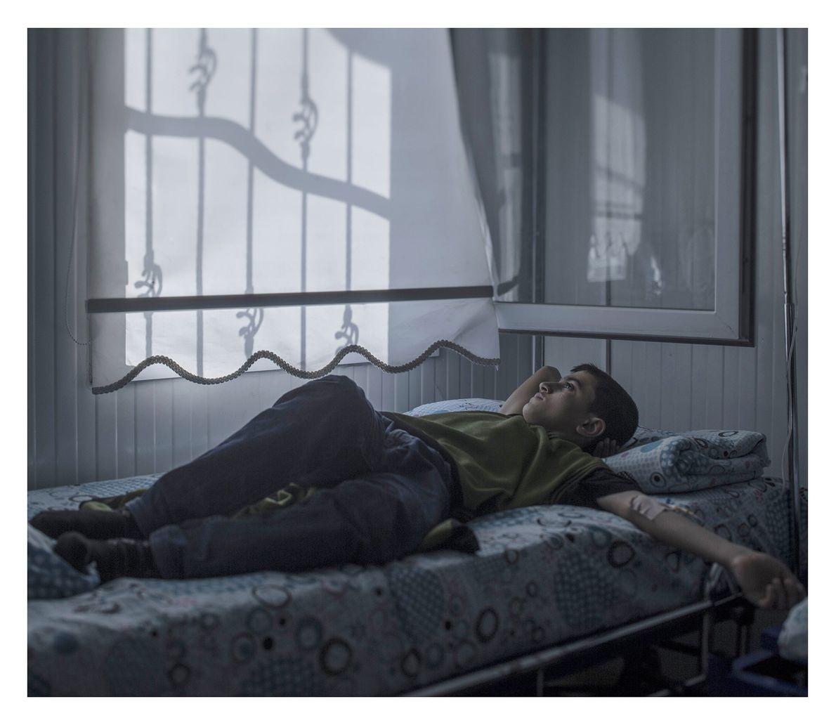 criança refugiada dormindo em um leito hospitalar