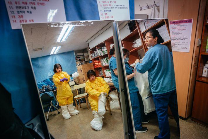 Jo An-na, 35 anos, e Seong Geum-ran, 33 anos, colocam os equipamentos de proteção de Nível ...