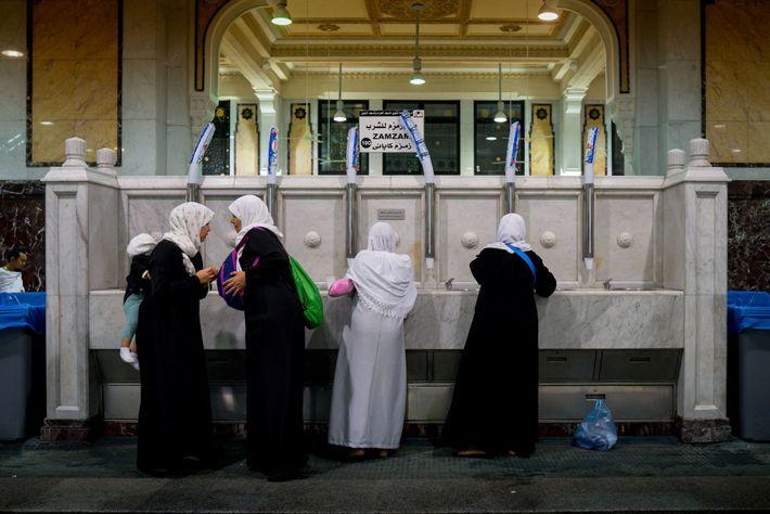 Mulheres coletam água de Zamzam de uma fonte na Grande Mesquita. Acredita-se que a água venha ...