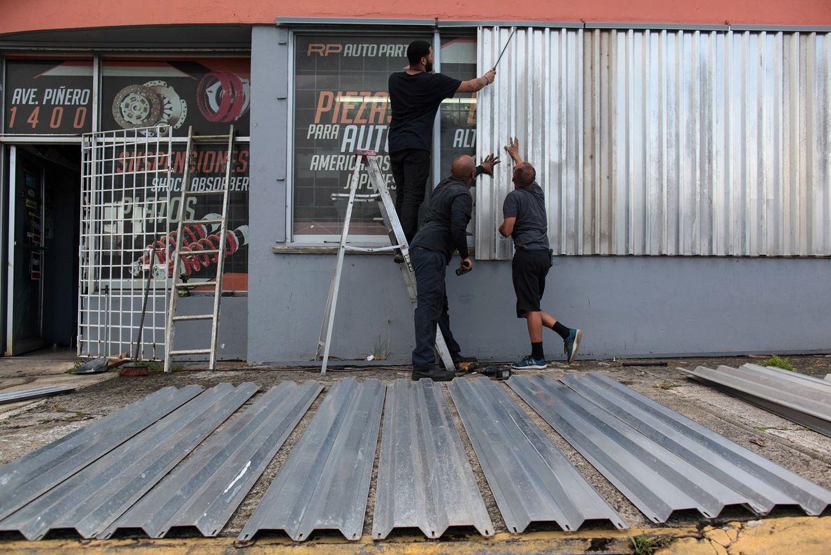 Homens cobrem as janelas de uma loja de peças de automóveis se preparando para o furacão ...