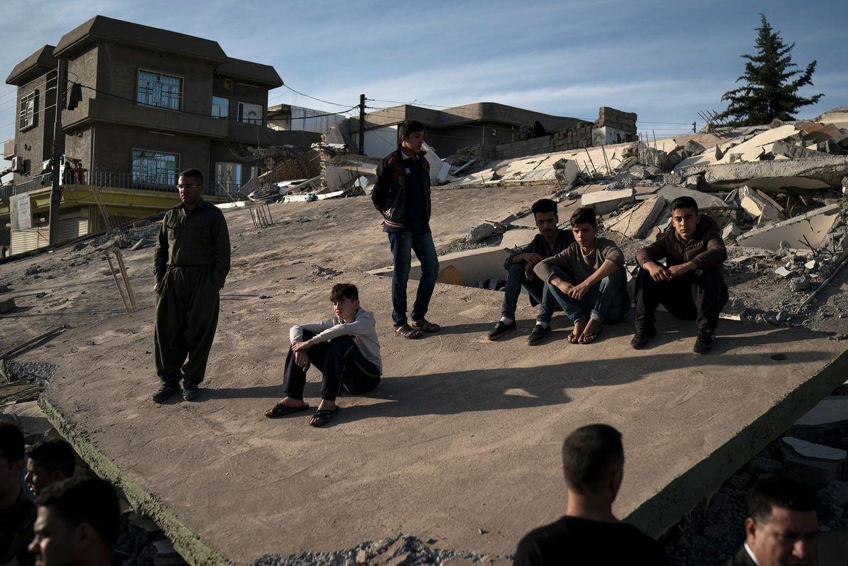 pessoas sentadas em telhado após o terremoto