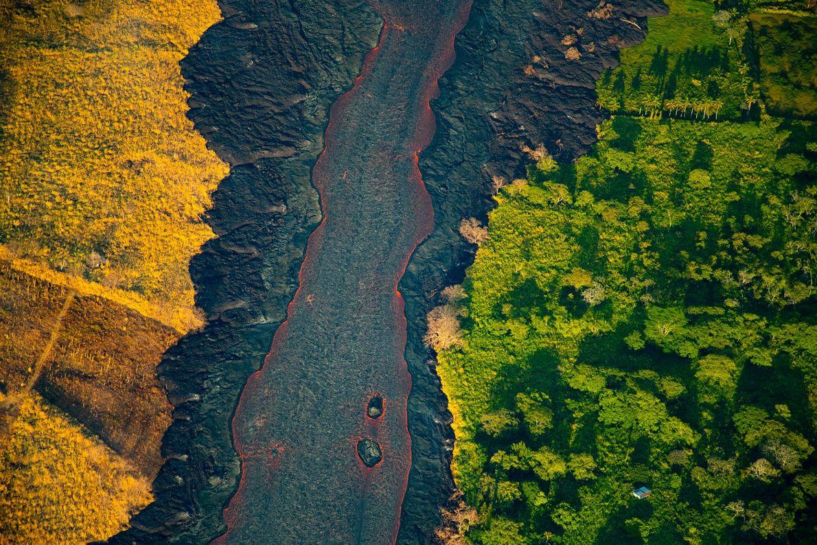 O sol nasce sobre um rio de lava que flui de uma fissura ativa. O rio ...