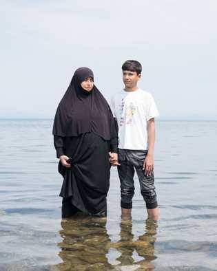 Kassim Hajem, de 14 anos, e sua mãe Ablam Saleh estão de pé da orla do ...