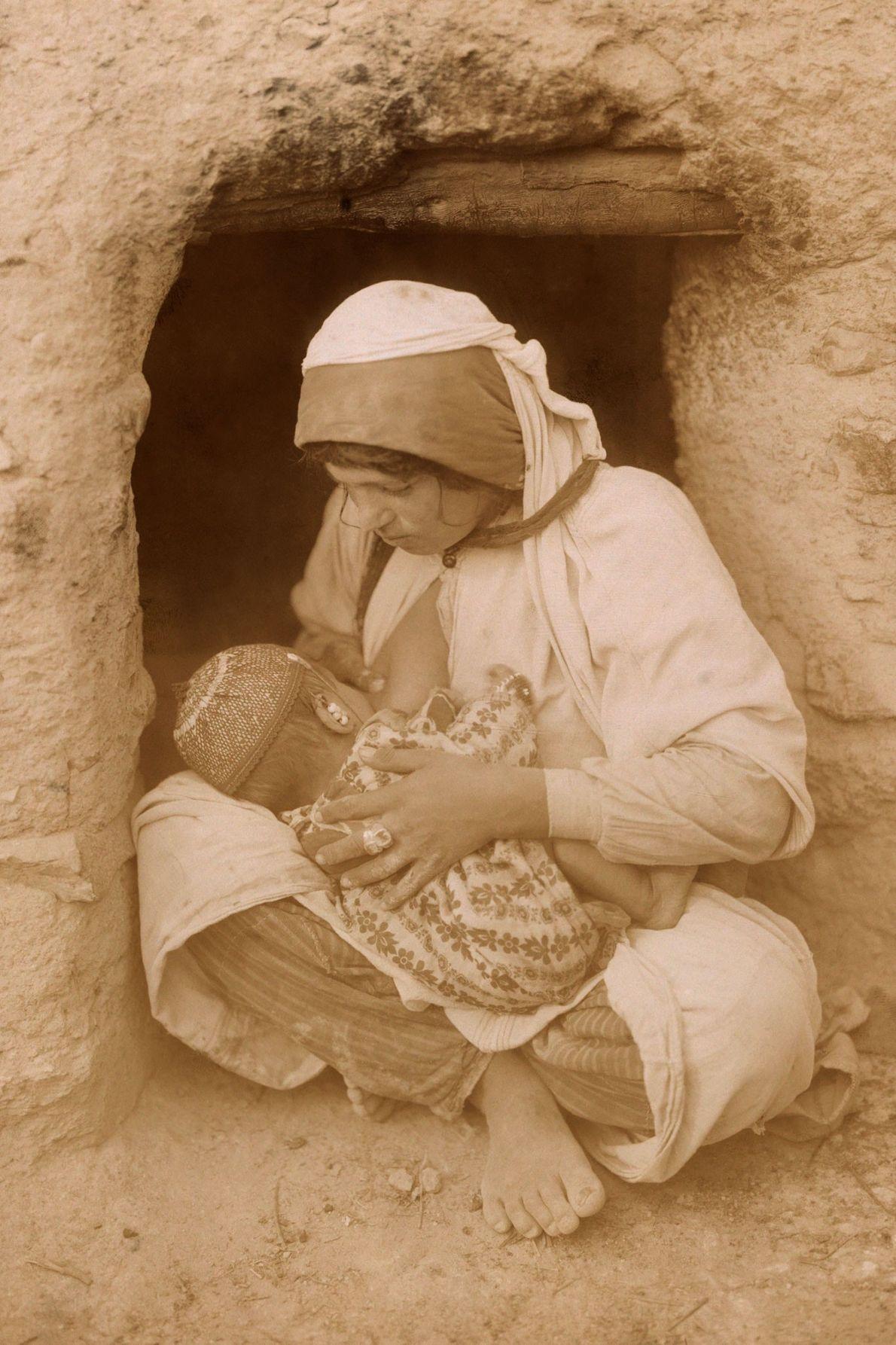 Uma mãe do Oriente Médio amamenta seu bebê sentada do lado de fora de sua casa.