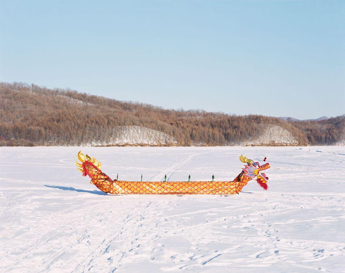 Um tradicional barco de dragão chinês sobre o rio Yichun congelado em Yichun, na província de ...