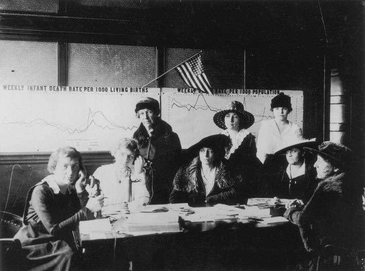 Mulheres alistam enfermeiras para ajudar durante a pandemia de gripe espanhola. Atrás delas, gráficos mostram as ...