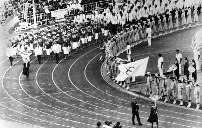 Dick Palmer, secretário da equipe olímpica da Grã-Bretanha, em primeiro plano à direita, carrega a bandeira ...