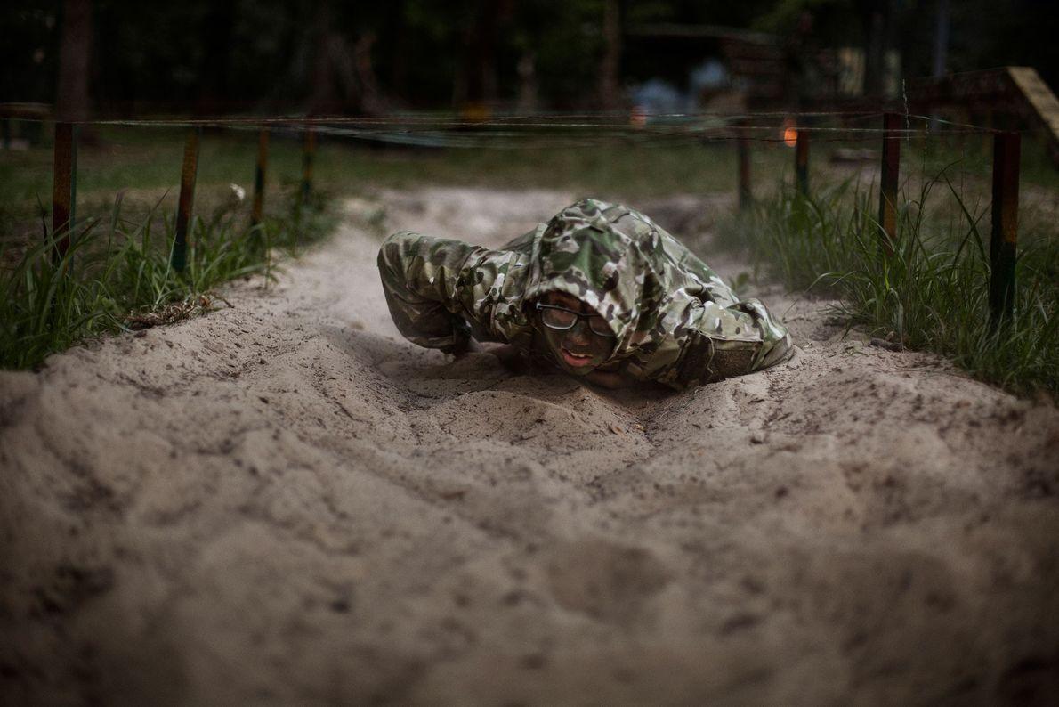 """Mathew, 11 anos, rasteja sob arame farpado durante um exercício militar no acampamento LIDER. """"Decidi participar ..."""
