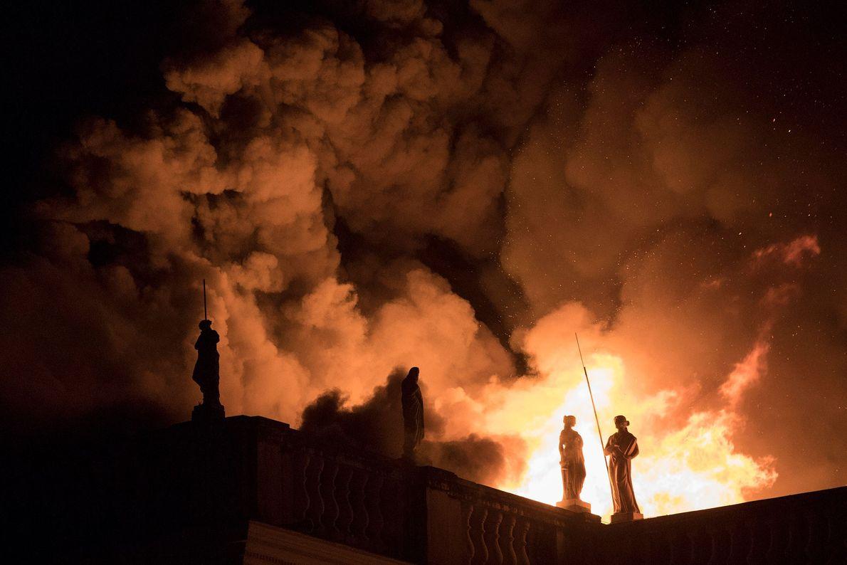 Chamas entram em erupção no teto do museu, iluminando as estátuas dos seus andares superiores. O ...