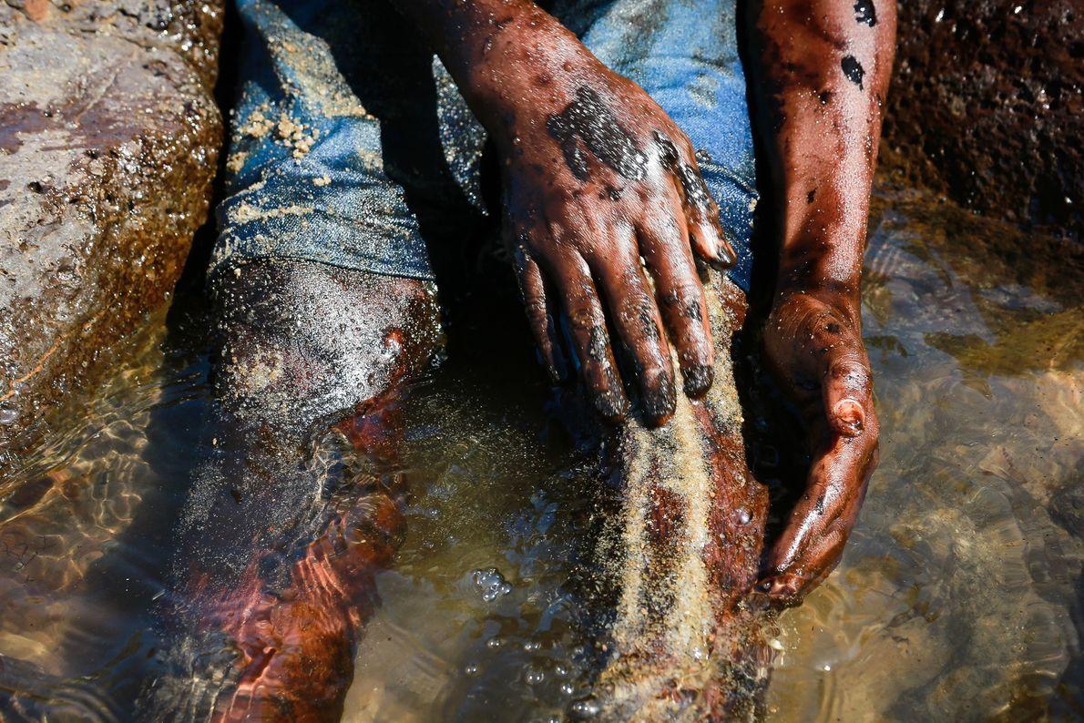 Garoto usa a areia da praia para tentar retirar o petróleo do corpo após atuar na ...