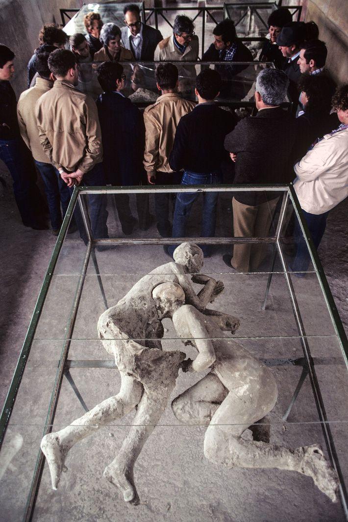 Um grupo estuda corpos solidificados na Casa do Criptopórtico enquanto percorre as ruínas em Pompeia. Além ...