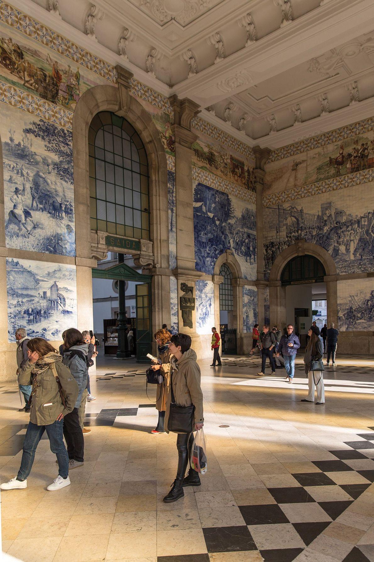 Os passageiros que chegam à estação de trem de São Bento, no Porto, impressionam-se com os ...