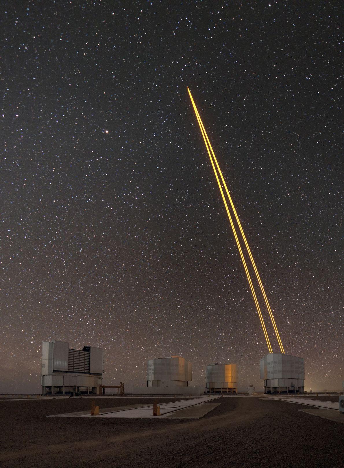 """A luz de laser cria uma estrela-guia artificial para o telescópio """"Very Large Telescope"""" do Observatório ..."""