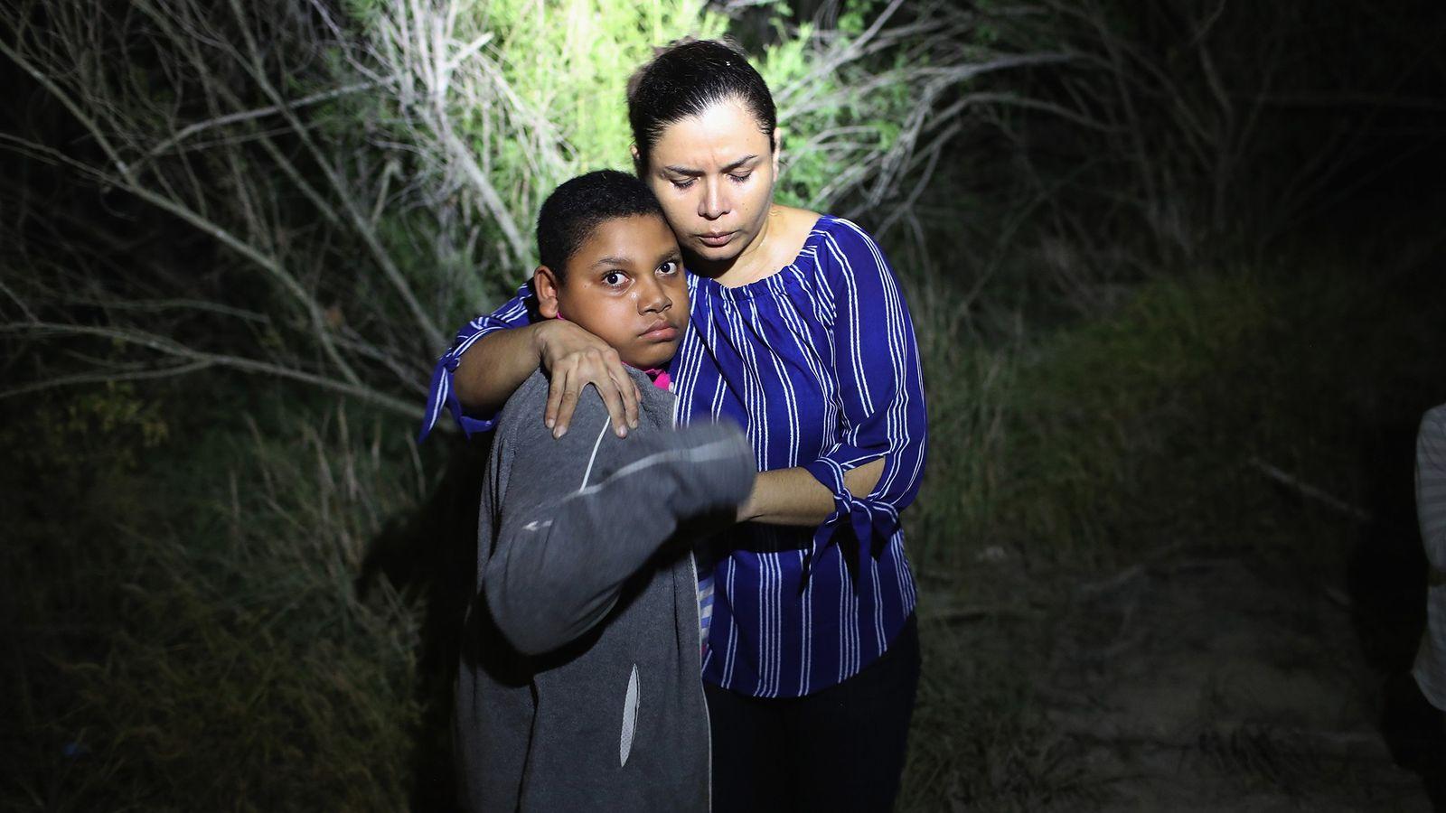 Um holofote da Patrulha da Fronteira dos Estados Unidos ilumina uma mãe e um filho de ...