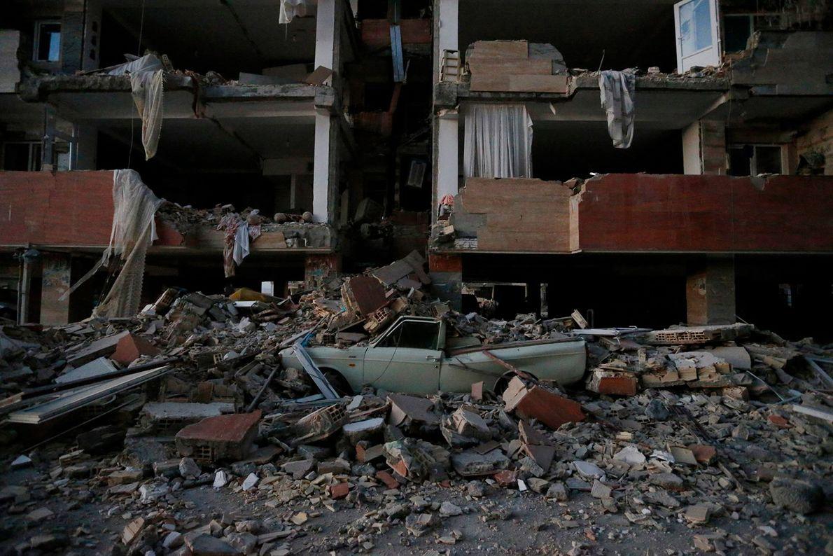 Carro sob escombros de prédio após terremoto no Irã