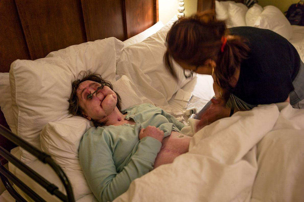 A mãe de Katie, Alesia, ajuda a filha a deitar em seu apartamento no Lar Ronald ...