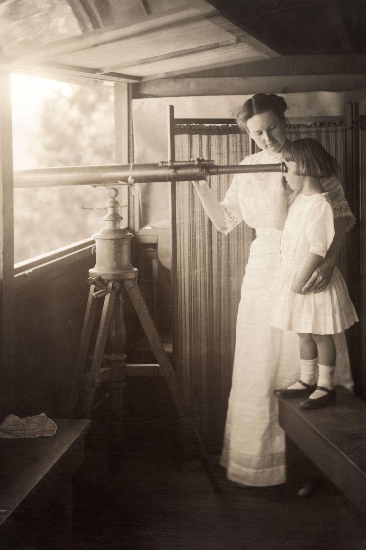 Mãe e filha observam um sinal de fogo através de um telescópio no Grand Canyon do ...