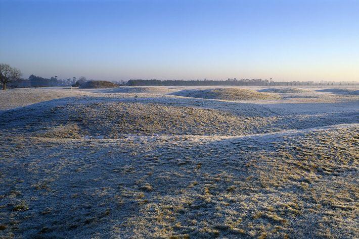Foto dos túmulos cobertos por uma geada em Sutton Hoo, ao amanhecer. Parte do cemitério descoberto ...