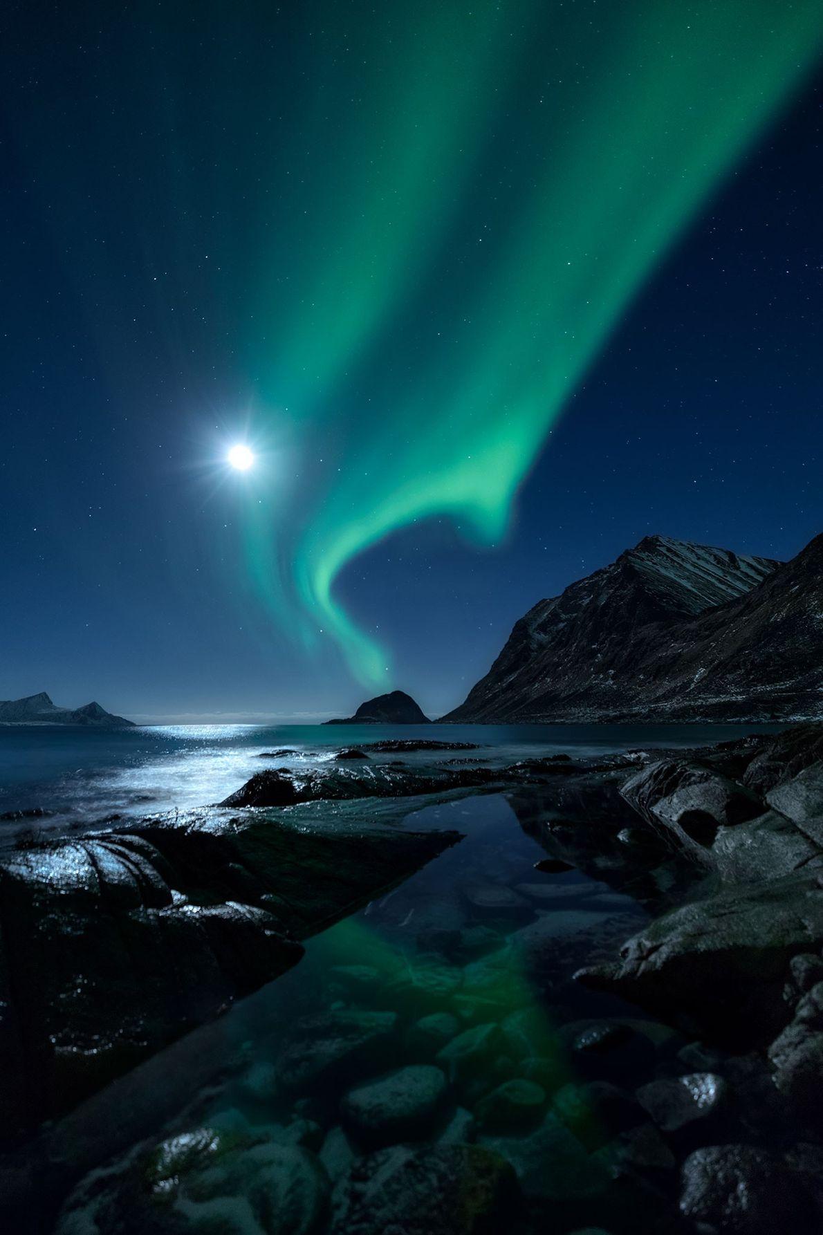 Sem ser ofuscada pela lua muito brilhante, a aurora boreal brilha sobre um fiorde no norte ...