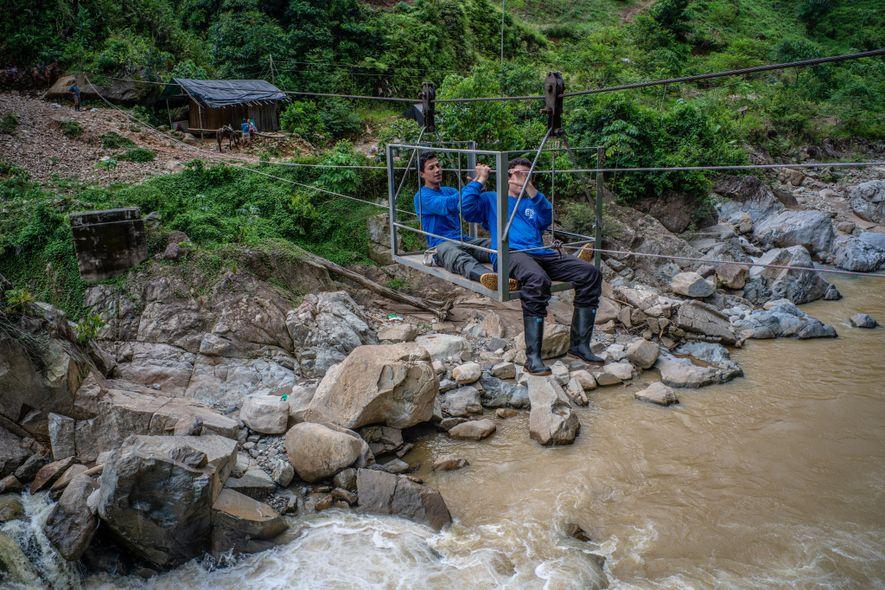 Dois biólogos da equipe cruzam o rio em tirolesas utilizadas pelos agricultores todos os dias.