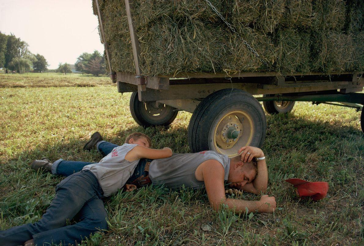Agricultores descansam em seus caminhões após um carregamento de palha em Delaware County, Iowa.