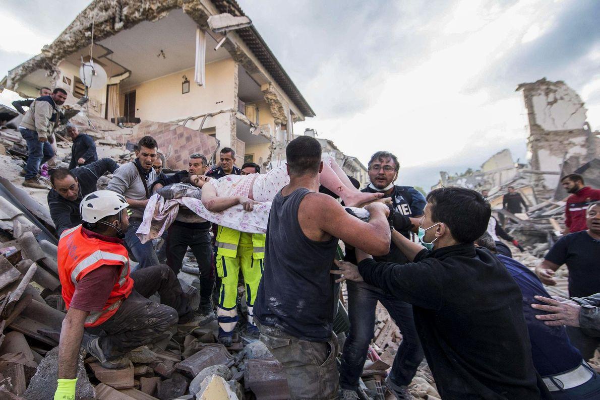 Os socorristas levam uma mulher ferida em meio aos escombros de edifícios colapsados em Amatrice, no ...
