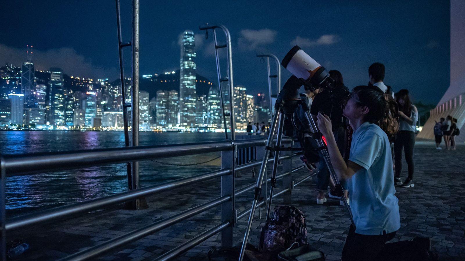 Observadores apontam telescópios para observar o eclipse da Lua de Sangue em Tsim Sha Tsui, Hong ...