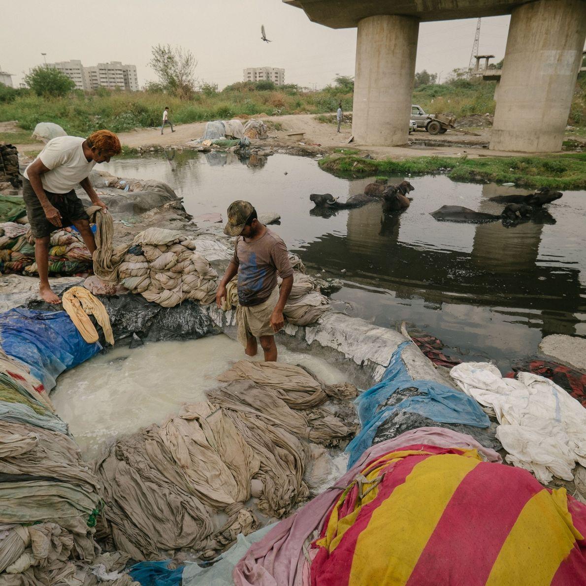 Homens lavam suas roupas em rio poluído