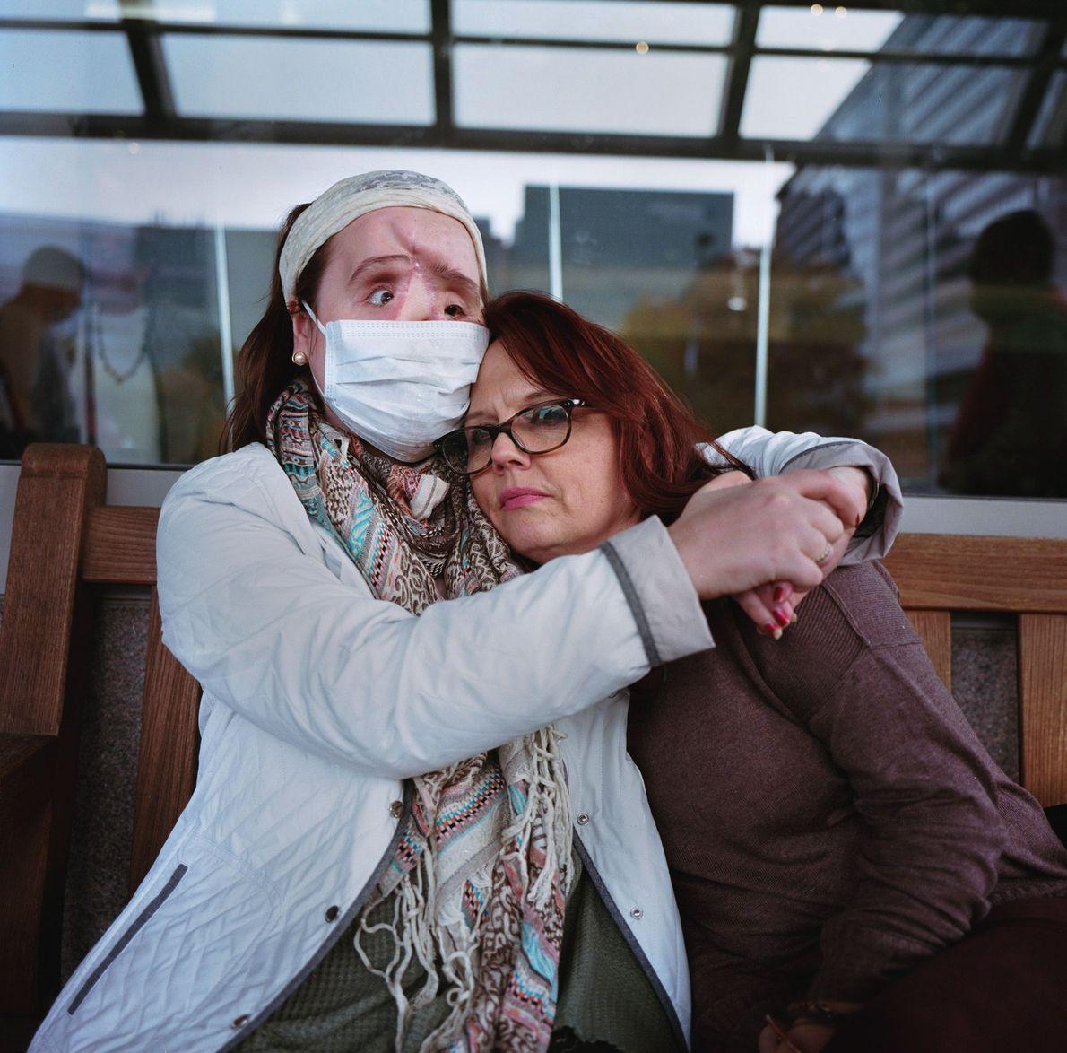Katie abraça a mãe do lado de fora da clínica oftalmológica da Clínica Cleveland após uma ...