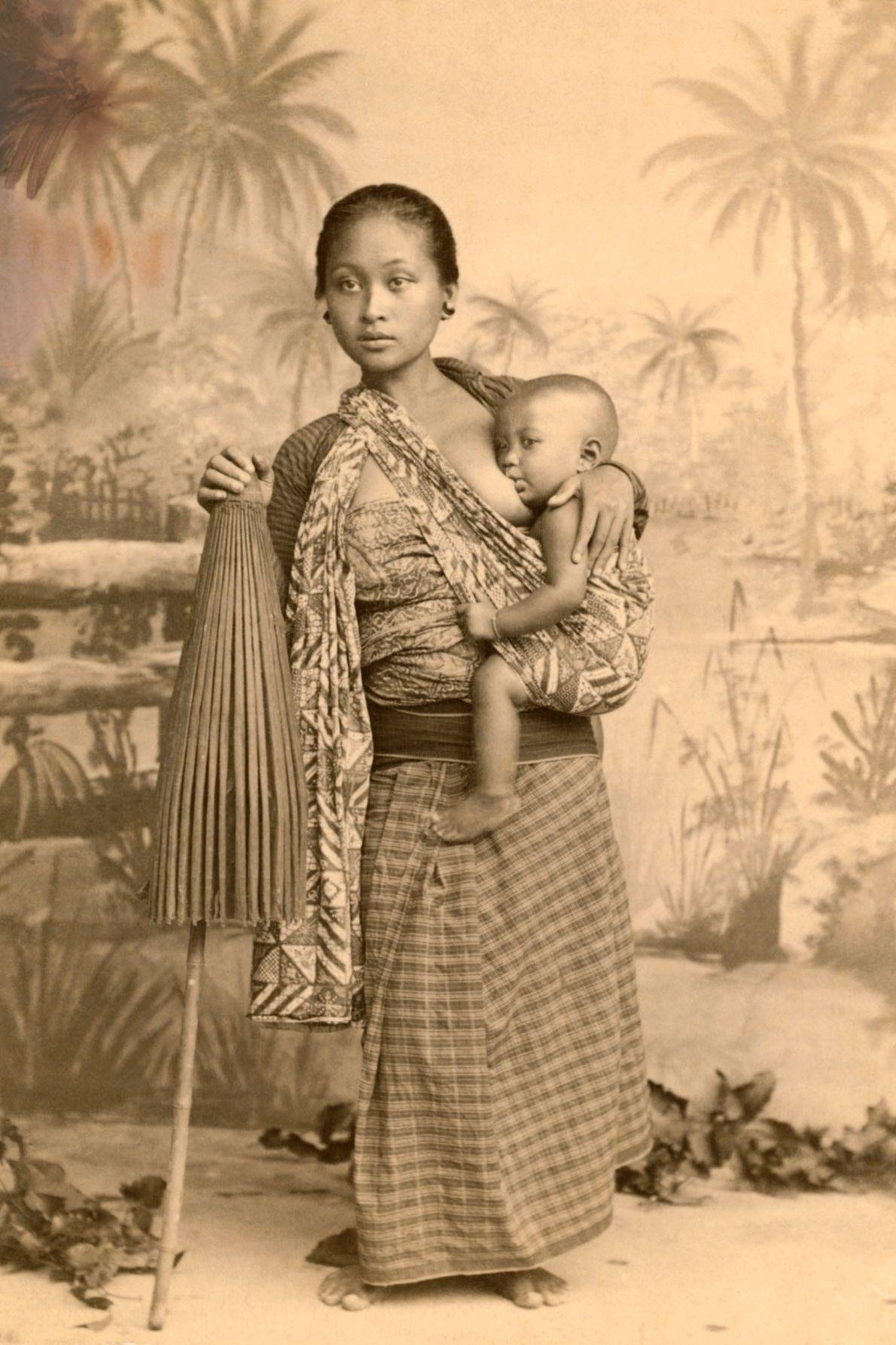 Uma mãe javanesa amamenta seu filho na Ilha Java, Indonésia.