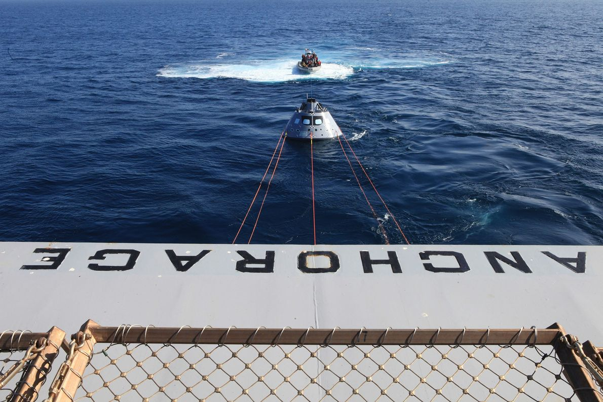 Visto na traseira do USS Anchorage, a cápsula de teste Orion é puxada por uma linha ...